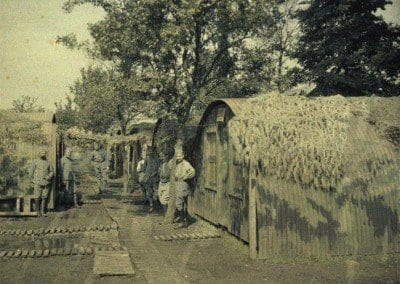 Camouflaged sheds situated on either side of a pathway.