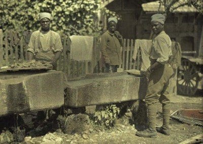 Senegalese servicemen washing linen in troughs.