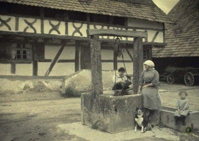 The Church. Wood-framed house. Two women, a girl, a dog near a well. Ballersdorf