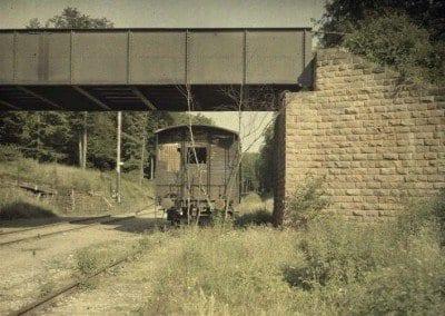 Railway car on a track under a metal bridge.