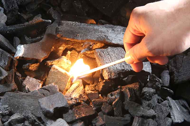 Lighting charcoal with a match