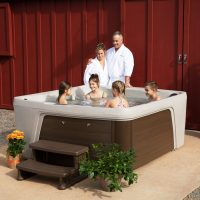 Parents standing behind children sitting in a smaller hot tub next to a barn