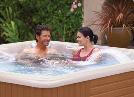 two people in a caldera spa in a backyard in Metairie, LA