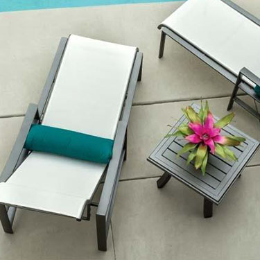 Two chairs and a table, they are close to a pool