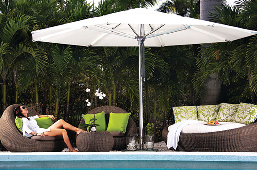 A lady lounging poolside with a Tuuci's umbrella shading her