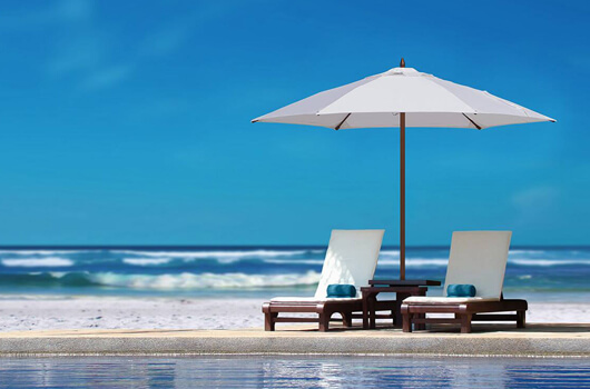 Tuuci's Ocean Master Classic mbrella shading two lounge chairs on the beach