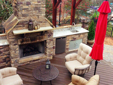 Outdoor fireplace with patio furniture and umbrella on a deck