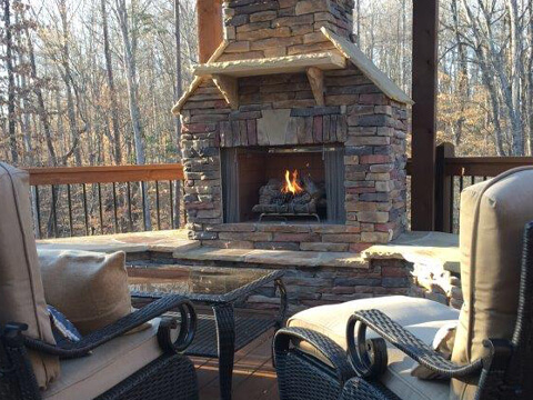 Burning outdoor fireplace with patio furniture and umbrella on a deck