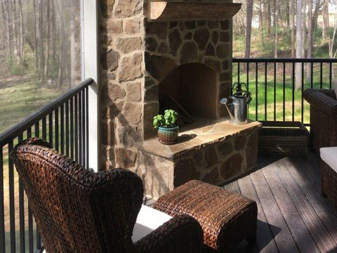 Outdoor fireplace with patio furniture on a deck viewing backyard