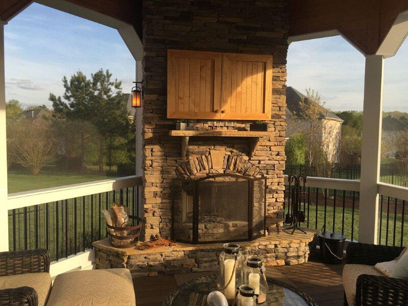 Outside fireplace and patio furniture on a newly installed deck