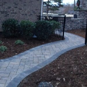 Stone walkway construction and installation along house