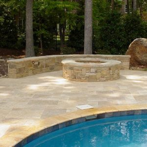 Fun Outdoor Living construction of a stone fire pit poolside
