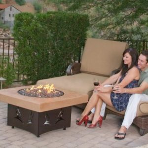 Couple drinking wine next to a fire table