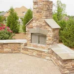 Brick and stone fireplace installation in backyard
