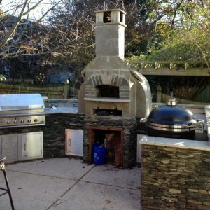 Outdoor kitchen with fireplace and built-in grill on patio