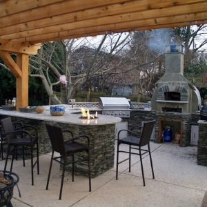Outdoor kitchen island with fireplace and table fire