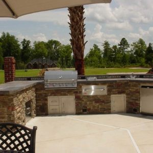 Stone outdoor kitchen and island with built-in grill