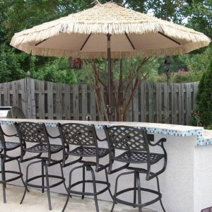 Outdoor kitchen island with bar stools and umbrella
