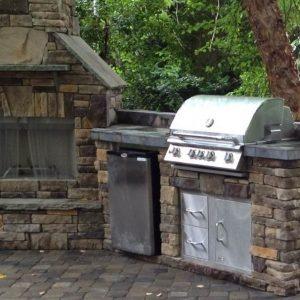 Stone kitchen island next to fireplace outside