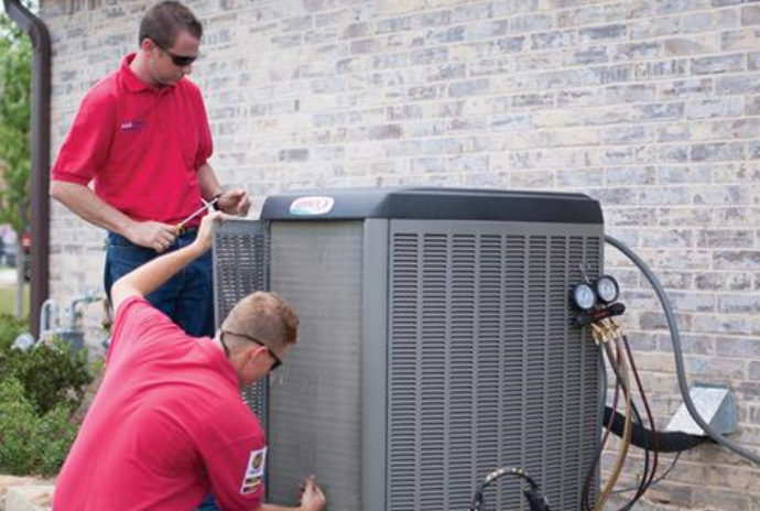 AC repairmen servicing air conditioning