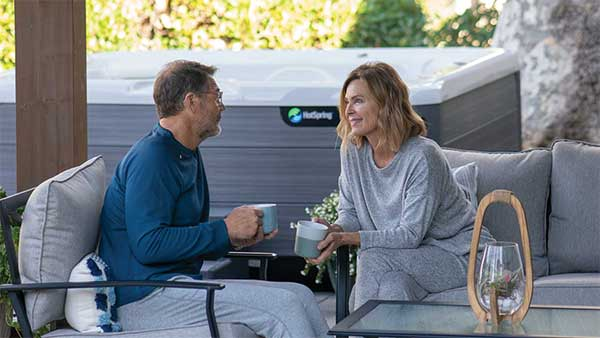 Wife and husband drinking coffee next to hot tub