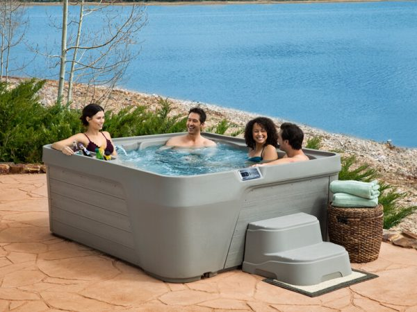Friends in a Freeflow portable hot tub lakeside