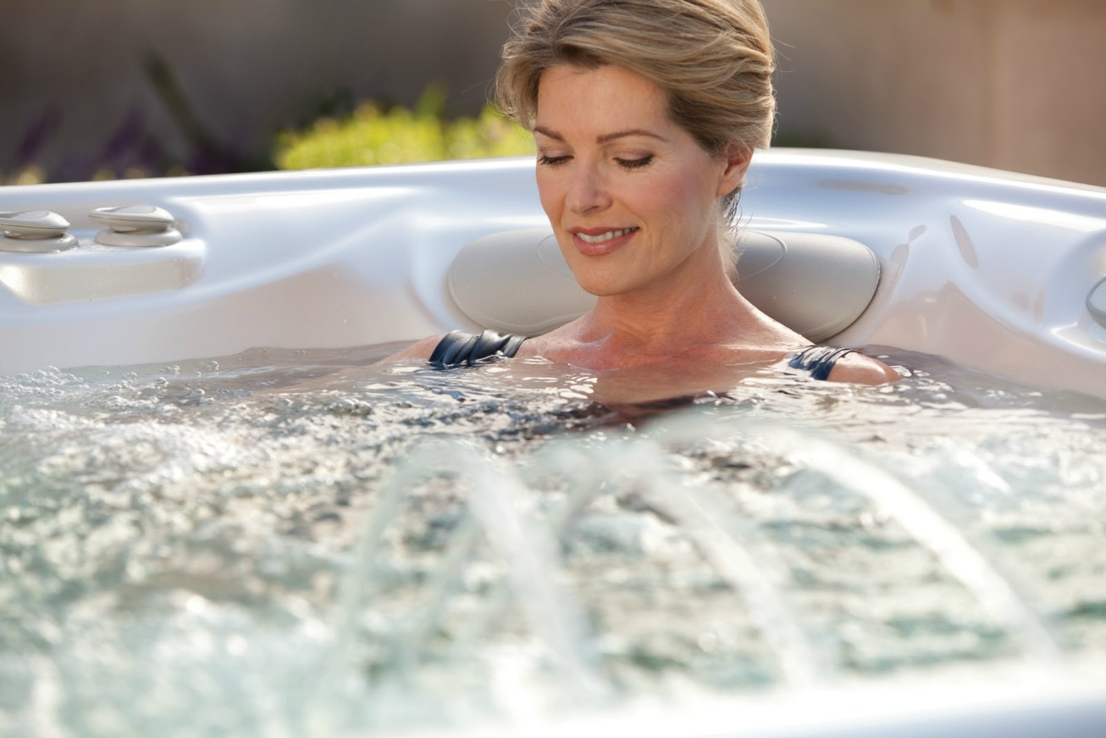 A woman relaxed and stress free in a hot tub