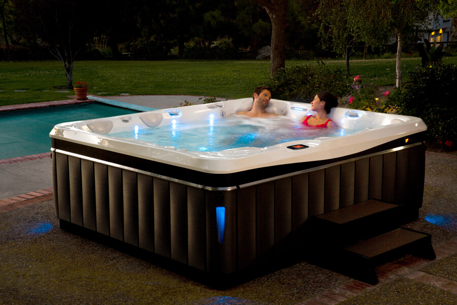 Couple in huge hot tub in backyard that also has a pool