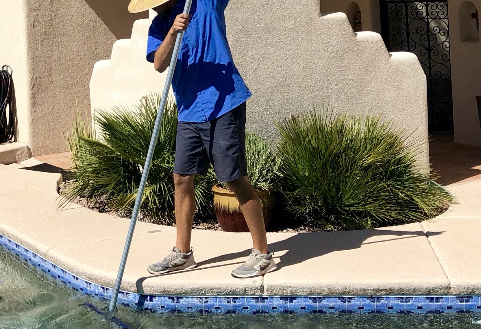 Man cleaning a pool in Tucson