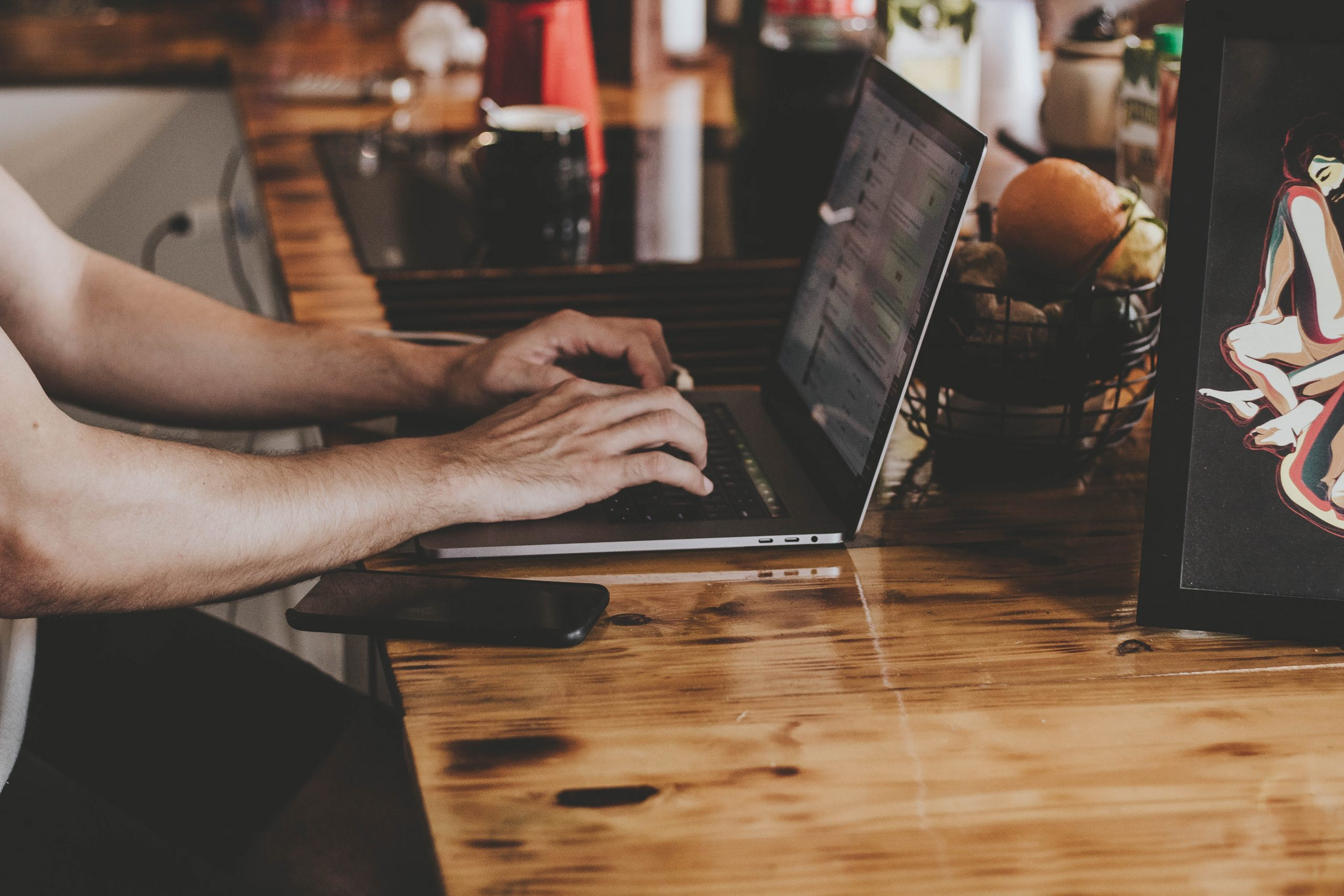 person-in-front-of-laptop-on-brown-wooden-table-2115217 (1)