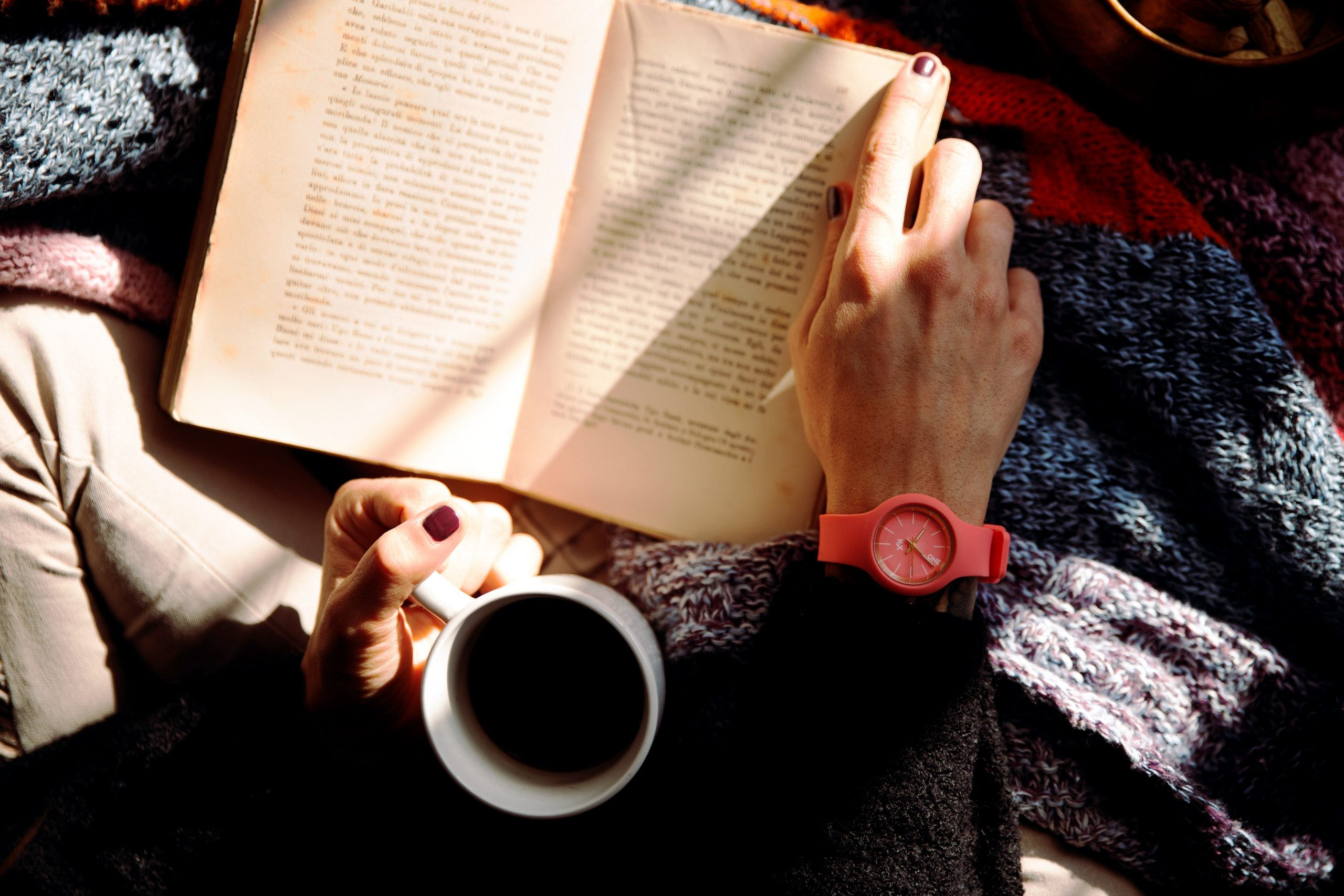 person-reading-book-and-holding-coffee