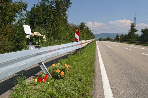 Fatal crash memorial site on the side of the road. Flowers to represent the loss of a loved one in a fatal car accident.