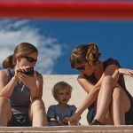 Trey, Heidi, and Alexandra Darriet watch a game of taureau piscine in Perols, France