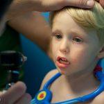 Dr. Cawley checks Trey's eyes, nose, & throat