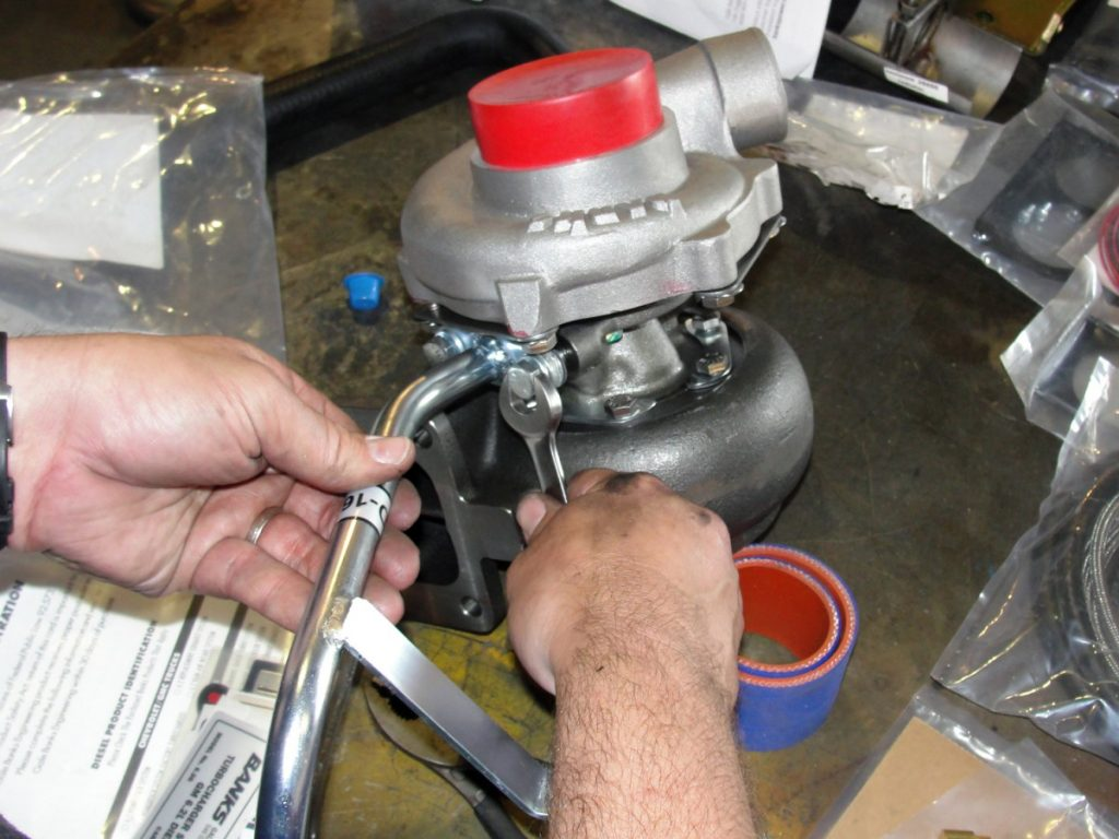 A drain tube used to connect the new lift pump spacer plate can now be mounted to the center bearing assembly of the turbo. (photo ref: hands, turbos w/ red caps)