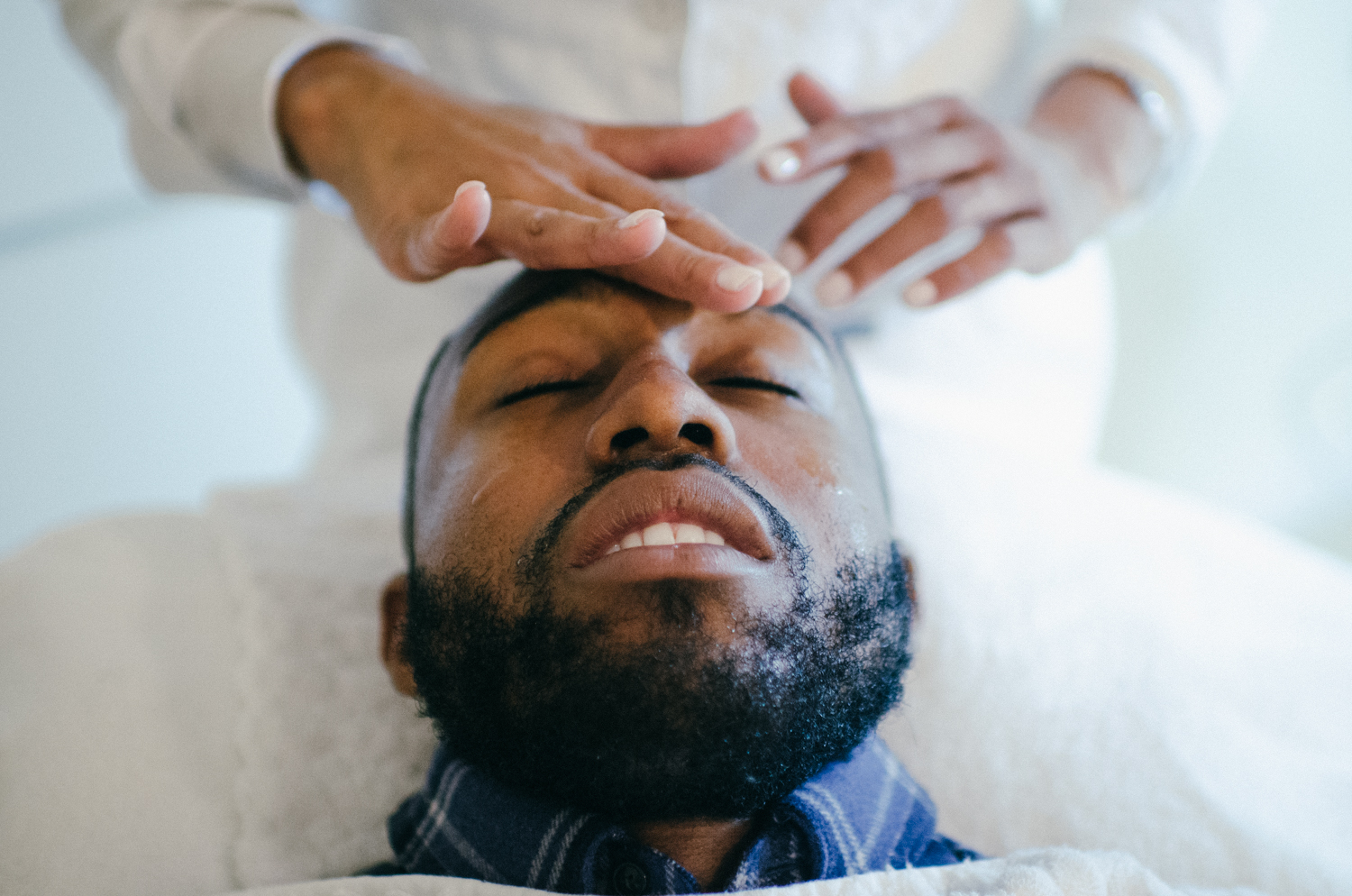 Images of Black man getting facial skin treatment
