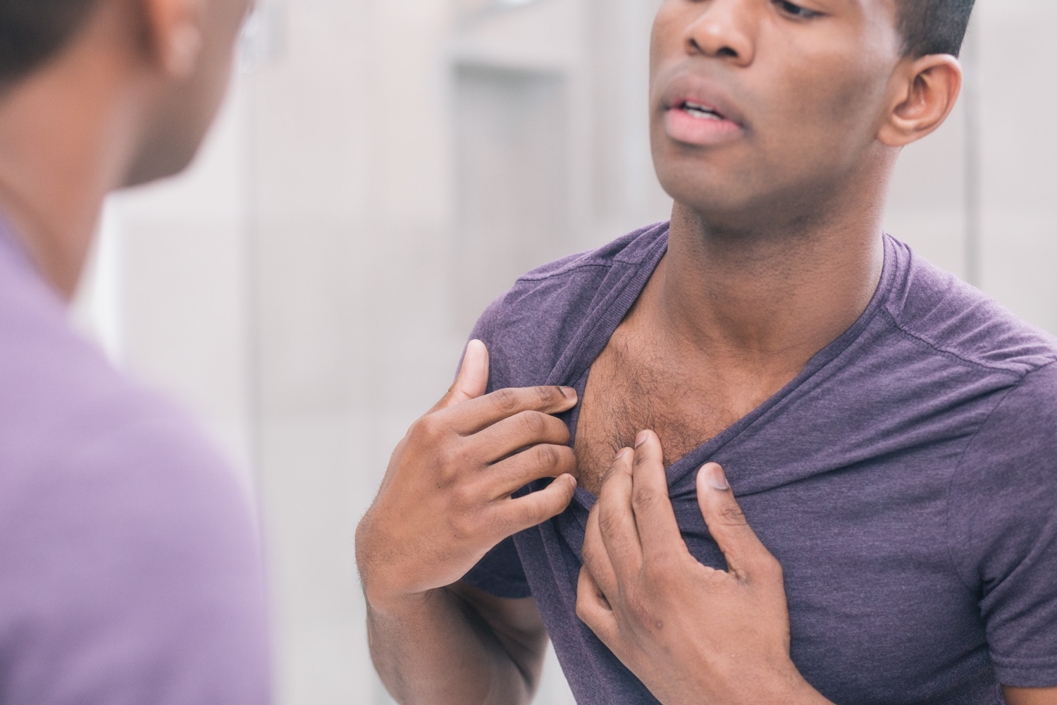 Man looks at his chest hair in mirror