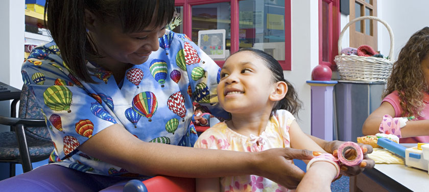 A full time school nurse smiles warmly as she assists an elementary school student in a classroom setting.