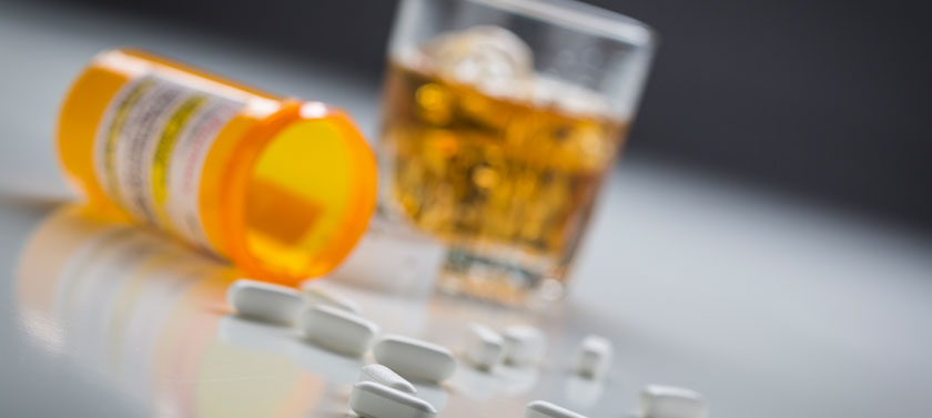 An overturned bottle of prescription pills and glass of alcohol rest on a table.