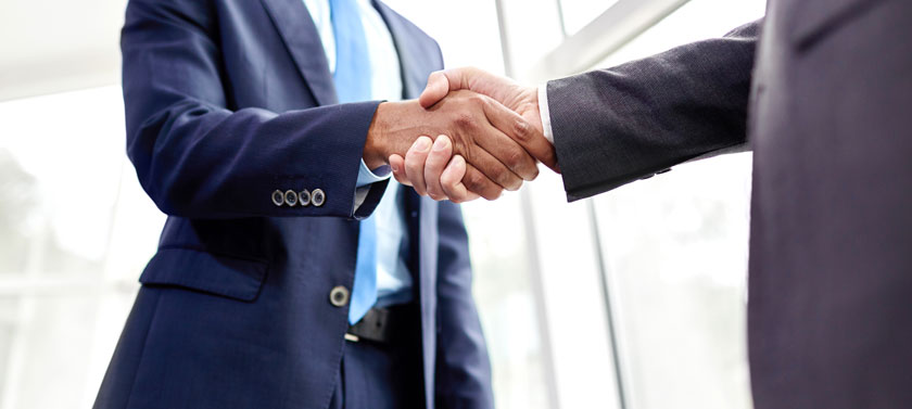 Two business professionals shake hands.