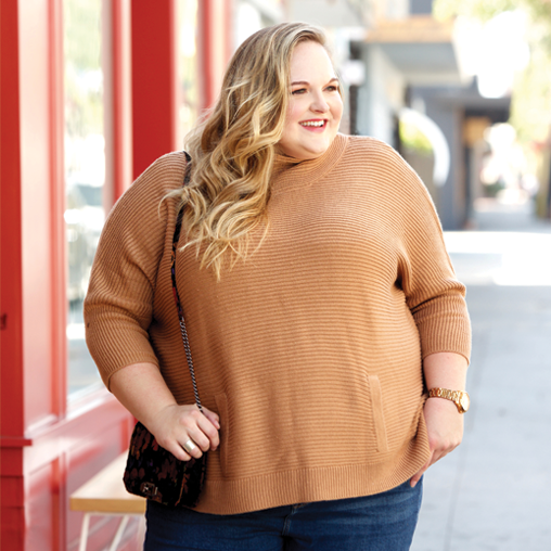reah norman wearing a plus size sweater and denim