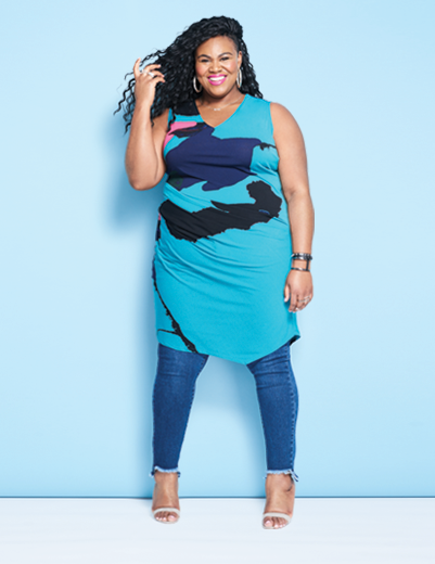 A woman wearing an outfit including plus size denim jeans and a turquoise dress
