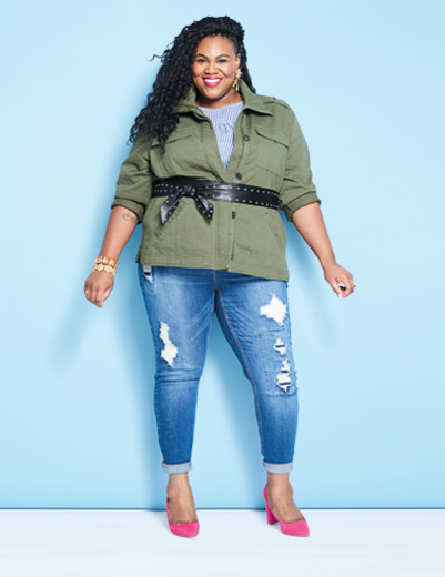 A woman wearing a plus size outfit including denim jeans, pink heels, and a belted jacket