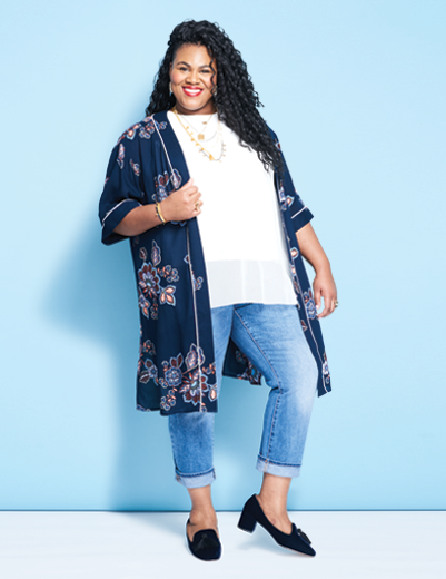 A woman wearing a plus size outfit including a floral cardigan, white shirt, and denim jeans