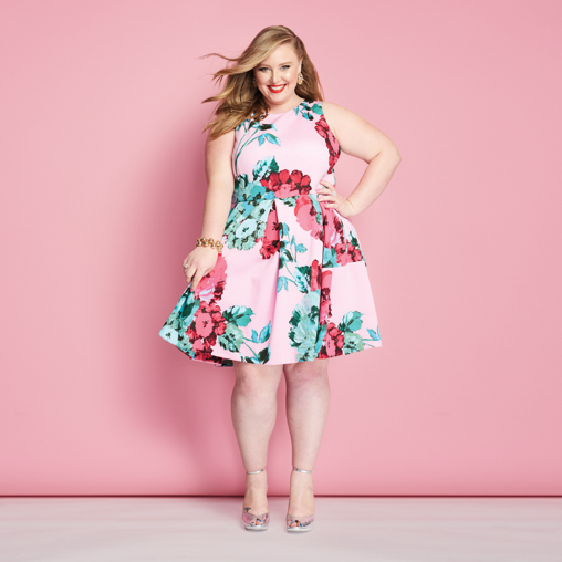 A woman wearing a plus size pink floral dress