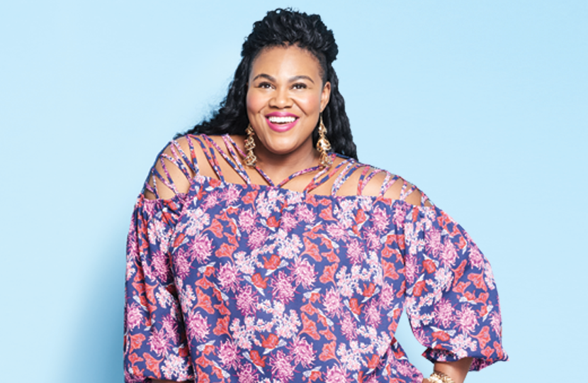 A woman wearing a plus size outfit with a flowy, floral patterned top