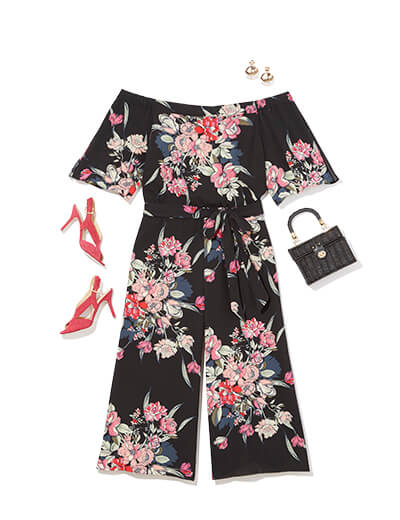 One of many boho outfits available at Dia&Co, this plus size outfit features a vivid floral pantsuit and red pumps.