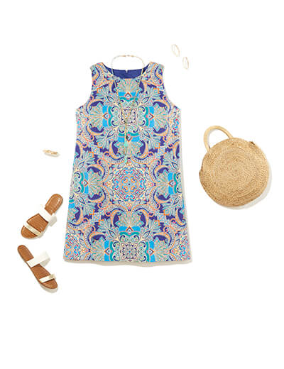 This preppy style outfit features a blue paisley designed shift dress, strappy sandals and straw bag.