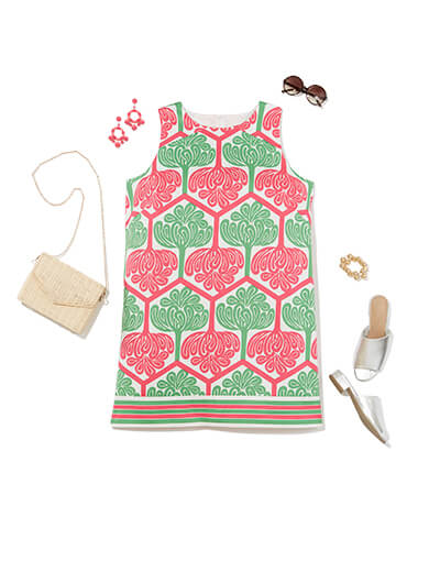 This preppy style outfit features a pink and green shift dress, ivory purse, and slip-on sandals.