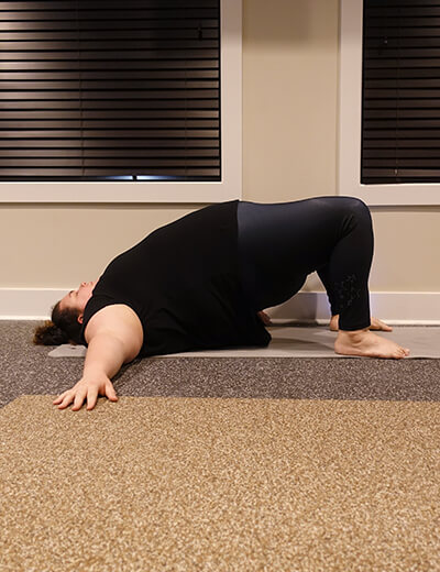 plus size woman doing yoga bridge